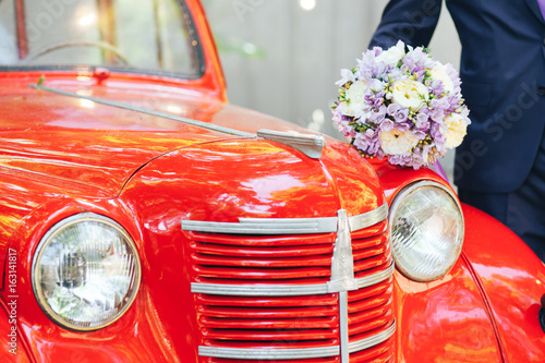 The groom is holding a wedding bouquet on the hood of a red retro car Fotobehang