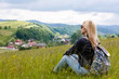 Beautiful woman sits on meadow in the mountains. The mountains and woodland in the background. Ukrainian Carpathians.