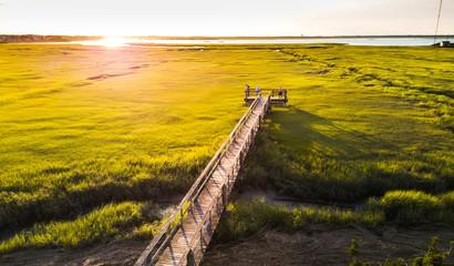 Fototapeta na wymiar Aerial view of wooden bridge over a swamp