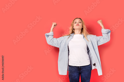 Young blonde girl shows her strength on red background Wallpaper Mural