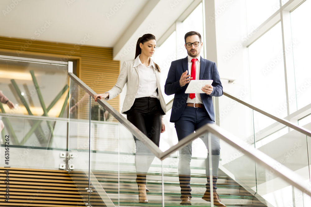 Fototapeta Young businesswoman and businessman walk down stairs in office with a tablet in his hand