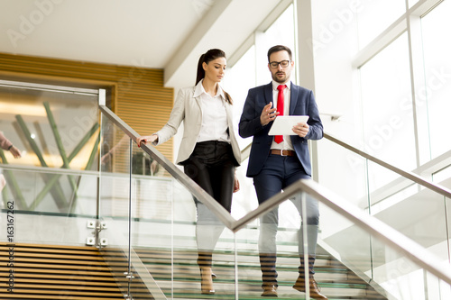Fotografie, Obraz  Young businesswoman and businessman walk down stairs in office with a tablet in