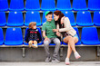 Leinwandbild Motiv Two girls and a boy are sitting in blue armchairs at the stadium. Two sisters miss his brother.