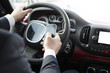 Close-up of a man's hand holding a smartphone. Businessman texting while sitting in a car. Holding a steering wheel and using a mobile phone.
