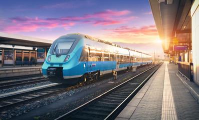Nowoczesny pociąg podmiejski wysokiej prędkości na stacji kolejowej i kolorowe niebo z chmurami o zachodzie słońca w Europie. Przemysłowy krajobraz z błękitnym pociągiem pasażerskim na kolejowej platformie. Tło kolejowe