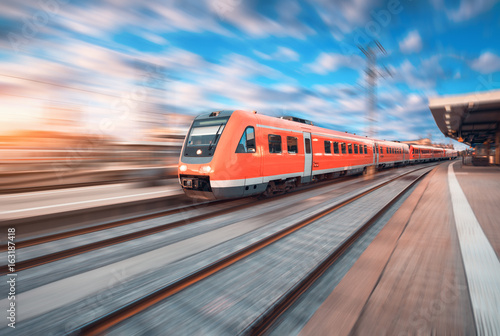 High speed commuter train in motion at the railway station at sunset in Europe плакат