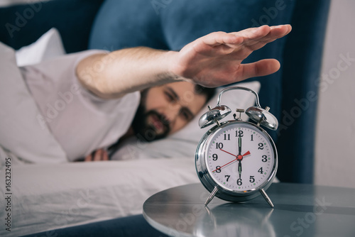 Plagát  Bearded young man trying to turn off alarm clock while lying in bed at morning