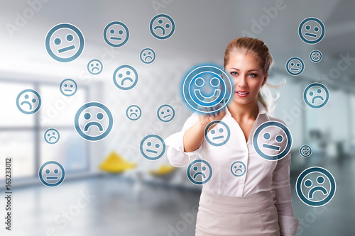 Fotografía  junge Geschäftsfrau wählt lächelnden Smiley aus vielen schlecht gelaunten aus