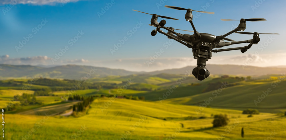 Fototapety, obrazy: A flying drone with camera with blured hills of Tuscany in the background