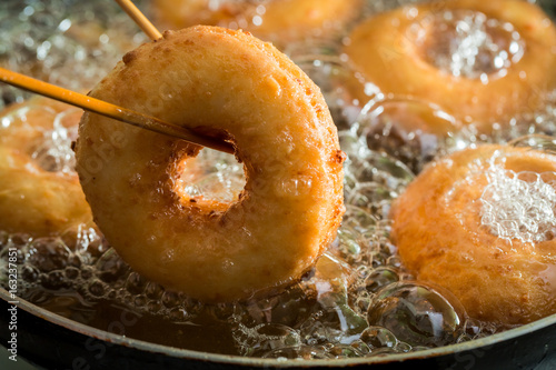 Fotografía  Frying homemade and sweet donuts on fresh oil