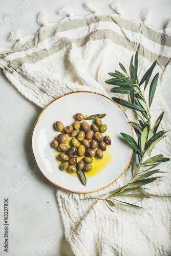 Foto auf Gartenposter Bar Pickled green Mediterranean olives in virgin olive oil on white ceramic plate and olive tree branch over grey marble background, top view