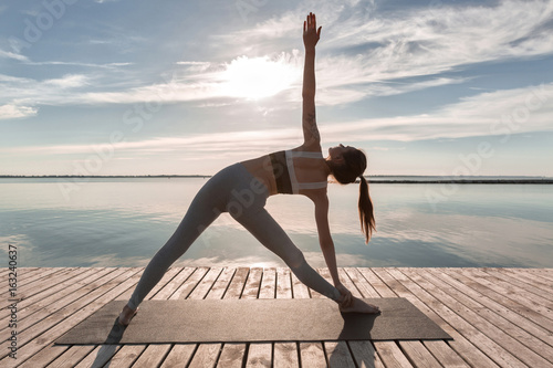 Spoed Foto op Canvas School de yoga Sports lady standing at the beach make yoga exercises.