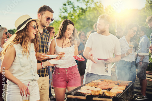 Friends having outdoor party and eating barbecue Wallpaper Mural