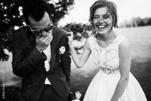 Fotografia, Obraz Happy bride and groom spending time in the park