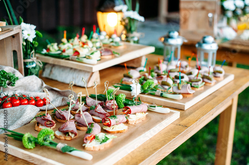 Foto auf Gartenposter Bar Beautiful catering banquet buffet table decorated in rustic style in the garden. Different snacks, sandwiches. Outdoor.