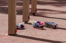 Two Pairs Of Childrens' Sneakers Lies On The Playground