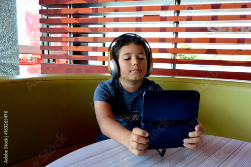 Photo  A boy with headphones is playing  video game