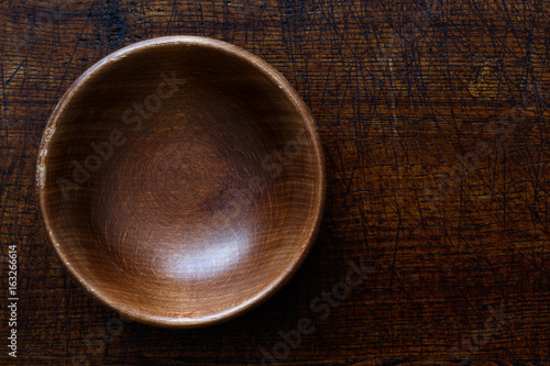 Photo  Empty dark wooden bowl isolated on dark brown wood from above.