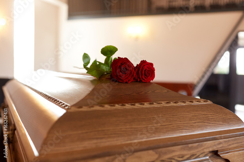 red rose flowers on wooden coffin in church Canvas Print