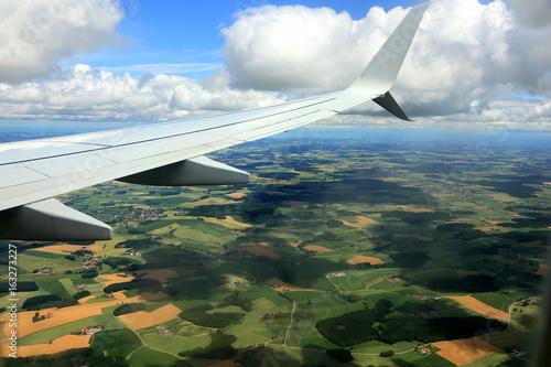 Widok wioski i pól z okna lecącego samolotu. - 163273227