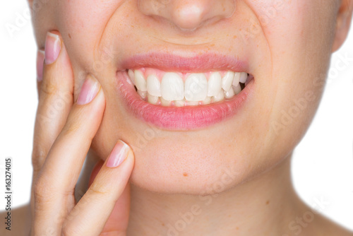 Fotografia  Closeup portrait of young woman achy girl suffering from terrible tooth pain, touching pressing her cheek