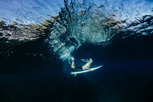 Man Swimming With Surfboard In...