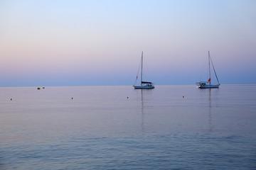 FototapetaŻaglówki na morzu przed wschodem słońca, na wyspie Rodos w Grecji.