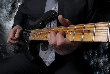 Fototapeta na wymiar neck of guitar with arm and hand playing the strings