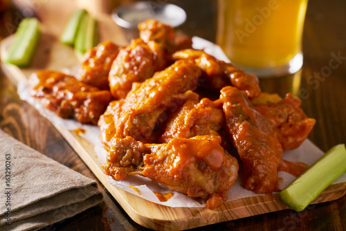 Photo  sauced buffalo chicken wings on wooden board with celery