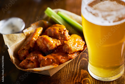 beer and hot buffalo chicken wings in tray with celery