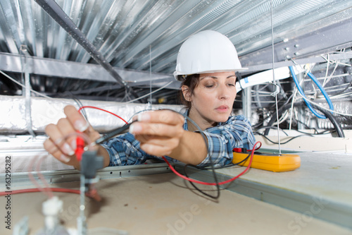 Photo  Woman checking spotlight with multimeter