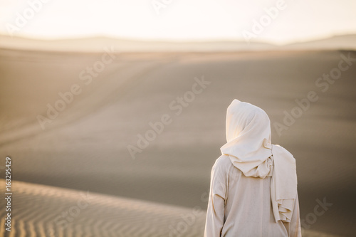 Jesus Christ looks out toward the sand dunes as the sun sets in the background Fototapet