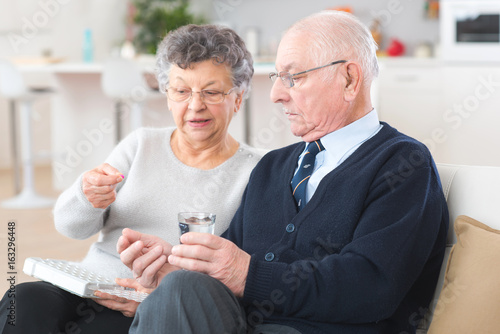 Elderly woman administering medication to husband from pillbox Wallpaper Mural