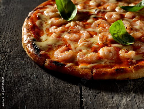 Pizza with shrimps on a wooden background