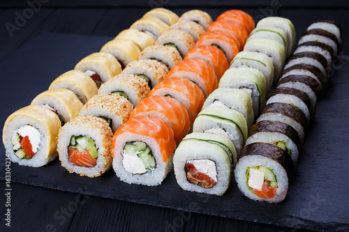 Colorful delicious set of sushi served on black slate, close up. Japanese cuisine, restaurant menu photo.