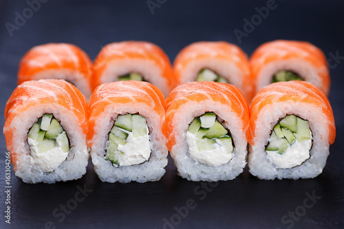 Tasty and fresh philadelphia sushi rolls served on black slate, close up Wallpaper Mural