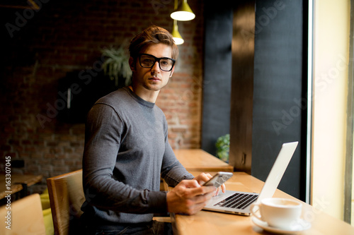 Photo  Young Man with a laptop looking through a window holding a coffee cup