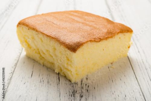 Fotografie, Tablou  side view sponge cake on white wood background