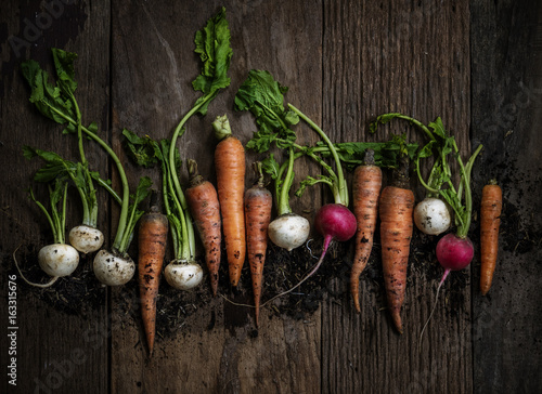 Foto auf Leinwand Gemuse Aerial view of carrots and beets on wooden table