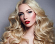 Leinwanddruck Bild - Beautiful young girl with luxurious light wavy hair close-up in the studio. Blonde - shiny, light long hair, curls. Makeup - arrows, red lipstick, pink blush. Cosmetics, hair care.