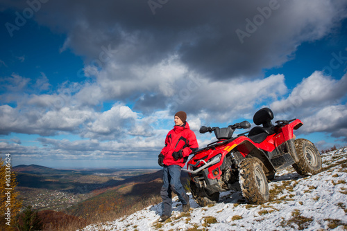 Atv quad bike near guy in winter clothes looking into the distance on snowy mountain slope. On the background blue sky with cirrus clouds, mountains and the town in the valley with copy space