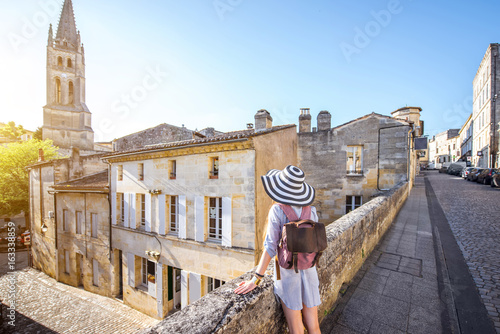 Canvas-taulu Young woman tourist walking old street at the famous Saint Emilion village in Bo