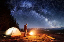 Male Hiker Have A Rest In His Camp Near The Forest At Night. Man Standing Near Campfire And Tent Under Beautiful Night Sky Full Of Stars And Milky Way. Long Exposure