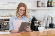 young waitress using digital tablet during work in coffee shop