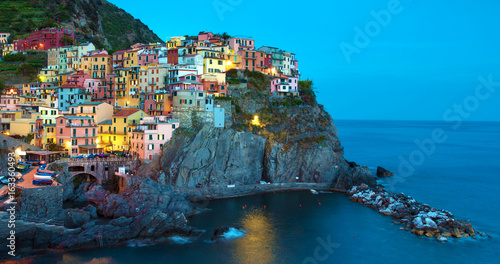 Aluminium Prints Europa Magical beautiful landscape with bright colored houses on the rock on the sea coast of Manarola in Cinque Terre, Liguria, Italy, Europe in the evening