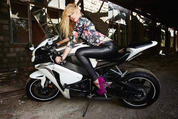 Obraz na płótnie Canvas sexy woman sitting on a motorbike