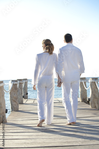 Couple De Dos couple qui marche de dos sur un ponton sur la mer - buy this stock