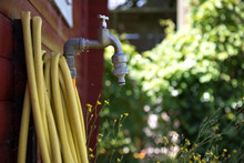 Faucet With Yellow Garden Hose Next To Red Garden Shed