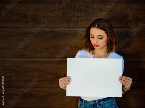 Sad young girl, holding empty sign board. Wooden background.