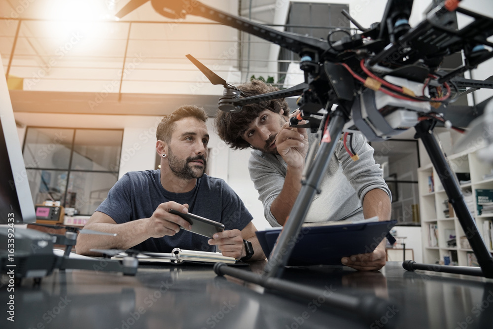 Fototapety, obrazy: Engineer and technician working together on drone in office